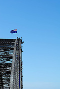 An Australian Flag flying atop the arch of the Sydney Harbour Bridge. Groups of tourists can be seen climbing the bridge. Sydney, Australia