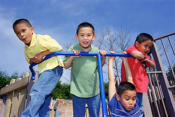 Group of boys leaning over and swinging on metal bar in children's playground,