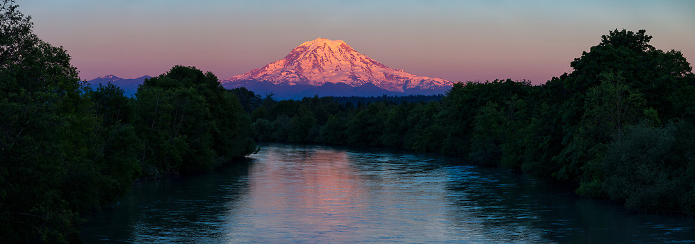 Mount Rainier reflects into the Puyallup River at sunset in this view from from Puyallup, Washington. Mount Rainier, with an elevation of 14,411 feet (4,392 meters), is the tallest mountain in Washington and the highest volcano in the Cascade Range. The Puyallup River is about 45 miles (72 kilometers) long, beginning on the west slope of Mount Rainier and emptying into Commencement Bay, which is part of Puget Sound.