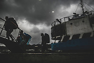 El Nido, Palawan, Philippines - July 16, 2019: At eight o'clock on a stormy morning, backpackers board a ferry in El Nido bound for Coron.