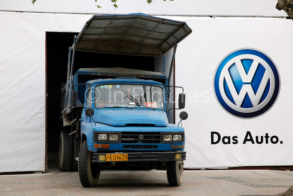 """A dump truck backs into an opening in a Volkswagen's  """"Das Auto""""  advertisement wall in Shanghai China, on  March 11, 2011.  China is now the fastest growing consumer market of almost everything, from cars to cosmetics."""