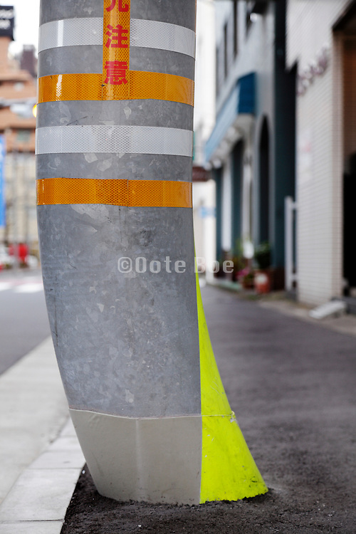 curved traffic pole with yellow warning for pedestrian Japan