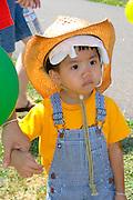 One year old Asian American boy dressed in bibs looking a bit baffled. Dragon Festival Lake Phalen Park St Paul Minnesota USA