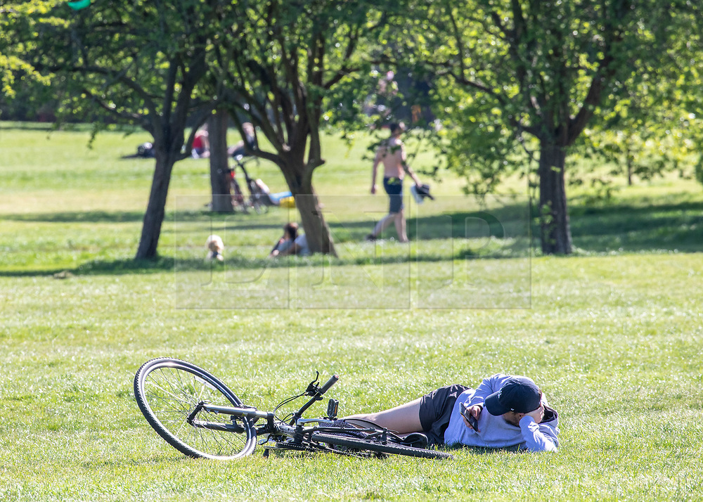 © Licensed to London News Pictures. 19/04/2020. London, UK. A cyclist relaxes in the sun on a warm Spring day as Police patrol Primrose Hill enforcing lockdown rules on social distancing and exercise as Ministers urge councils to keep parks open to the public during lockdown. Photo credit: Alex Lentati/LNP