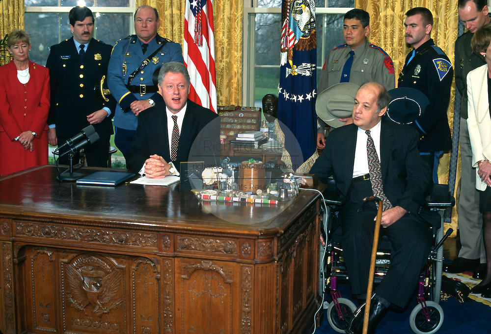U.S. President Bill Clinton discusses gun control during his weekly address in the Oval Office of the White House as former Reagan Press Secretary James Brady looks on March 5, 1997 in Washington, DC.