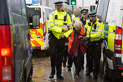 Colnbrook, UK. 27th September, 2021. Metropolitan Police officers arrest Insulate Britain climate activist Reverend Sue Parfitt who had blocked a slip road from the M25 at Junction 14 close to Heathrow airport as part of a campaign intended to push the UK government to make significant legislative change to start lowering emissions. The activists are demanding that the government immediately promises both to fully fund and ensure the insulation of all social housing in Britain by 2025 and to produce within four months a legally binding national plan to fully fund and ensure the full low-energy and low-carbon whole-house retrofit, with no externalised costs, of all homes in Britain by 2030.