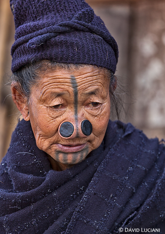 When Apatani women were young, small nose plugs were insert into an incision made near the alar crease of their nose. As time went by, these plugs were replaced with larger wooden plugs.