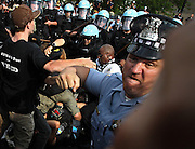 A Chicago police officer punches an anti-NATO protester as the two groups clash at the end of a march Sunday, May 20, 2012 outside the convention center where the world summit was underway. The officer behind him falls to the ground after being hit with a stick by another protester.
