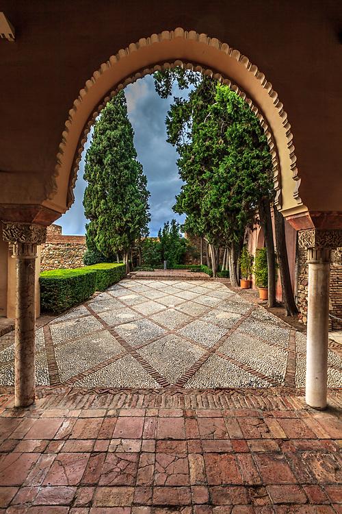 Caliphal arches lead into the garden in the Torre de Maldonado in  Alcazaba of Málaga in Malaga, Spain. The Alcazaba of Málaga is the best-preserved Moorish fortress-palace in Malaga, Spain.