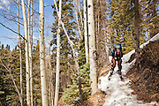 Peter Richardson skis down a narrow path of snow on a spring approach to the Ridgway Hut, San Juan Mountains, Colorado.
