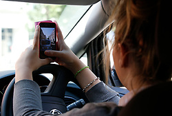 PICTURE POSED BY MODEL<br /> A woman takes a photo on her phone whilst driving.