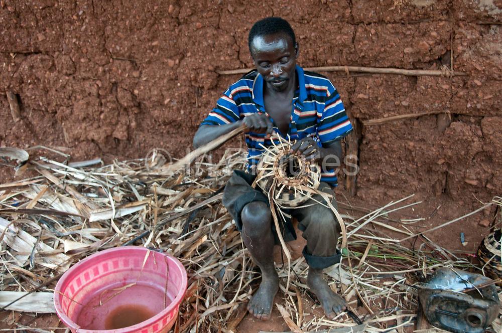 Rwanda February 2014. Kigali. Rutongo. Jari secteur, Nyamitanga cellule.  A man sits on a stool by the mud wall of his home weaving banana leaves to make vases.