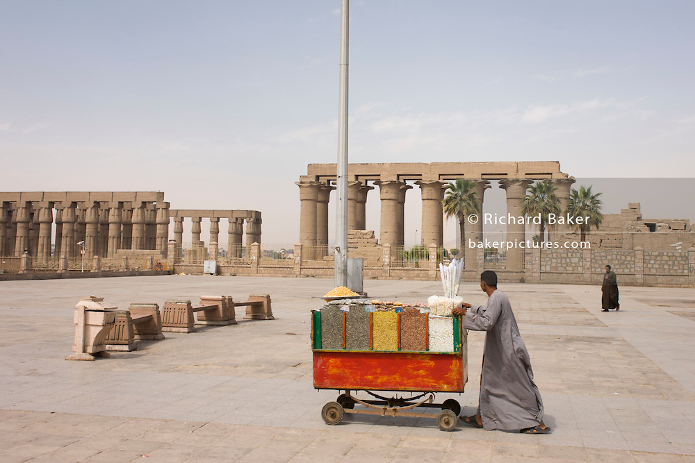 A nuts and seeds stallholder pushes his cart towards arriving tourists in front of the ancient Egyptian columns of Luxor Temple, Luxor, Nile Valley, Egypt. The temple behind was built by Amenhotep III, completed by Tutankhamun then added to by Rameses II. Towards the rear is a granite shrine dedicated to Alexander the Great and in another part, was a Roman encampment. The temple has been in almost continuous use as a place of worship right up to the present day.
