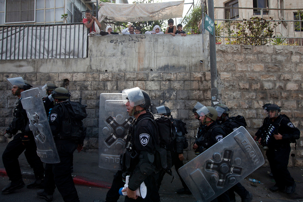 Palesinians watch from their house as Israeli anti-riot policemen walk by during clashes with Palestinian stone throwers in the Arab neighborhood of Wadi al-Joz in east Jerusalem, on September 24, 2010. Israeli police tightened restrictions for Muslim worshippers attending Friday prayers at the al-Aqsa mosque after violence erupted earlier this week following the killing of a Palestinian man by an Israeli security guard in the east Jerusalem Arab neighborhood of Silwan.