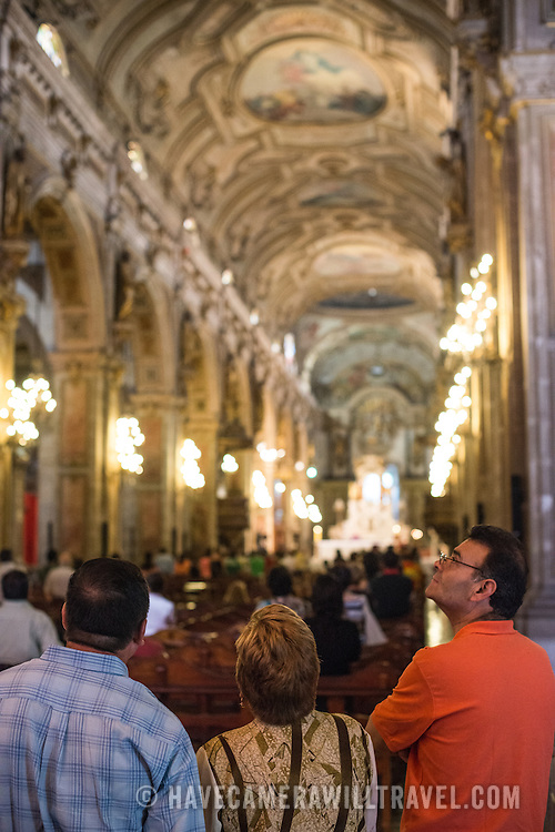 Visitors admire the ornately decorated interior of the Metropolitan Cathedral of Santiago (Catedral Metropolitana de Santiago) in the heart of Santiago, Chile, facing Plaza de Armas. The original cathedral was constructed during the period 1748 to 1800 (with subsequent alterations) of a neoclassical design.
