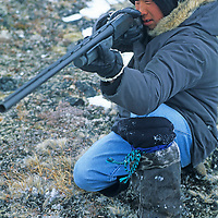Young Inuit hunter Romeo Palluq aims his shotgun at a snowshoe on the tundra of Baffin Island, Nunavut, Canada.