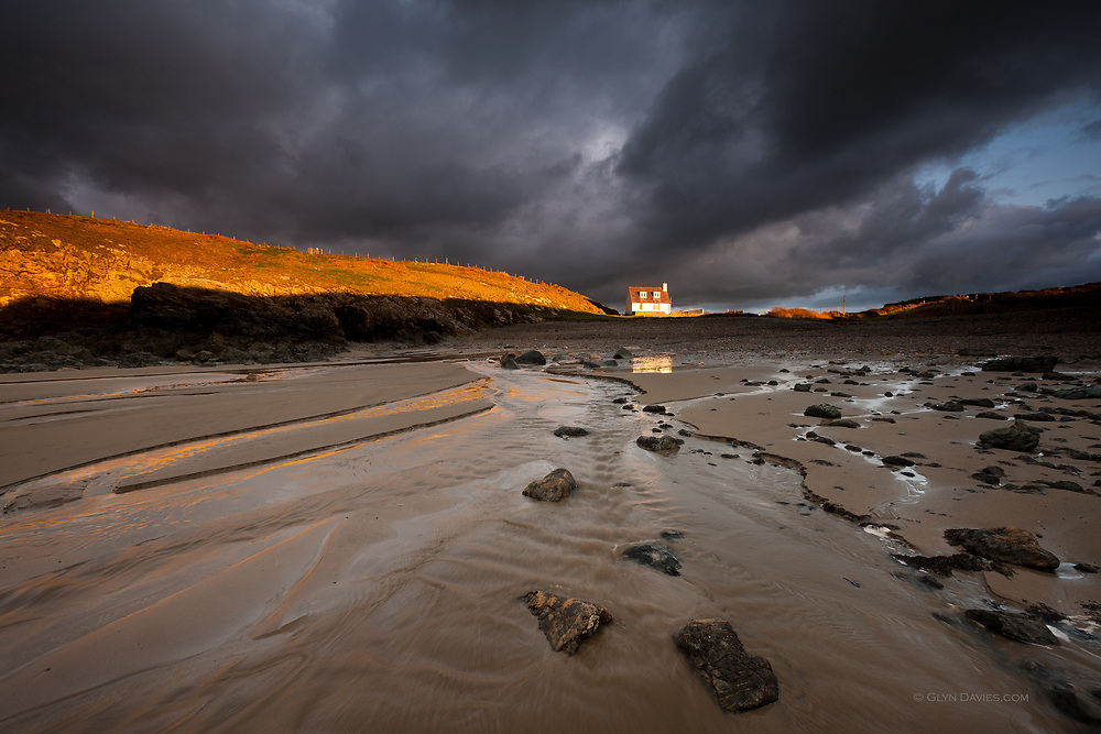"""International Color Awards 2016 - Nominee in """"Nature"""" category<br /> <br /> A solitary house bathed in late afternoon sunlight in dramatic weather overlooks this secluded little cove on North Anglesey, where streams run down to the sea."""