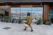 A takeaway delivery rider walks past a banner that shows a premium rooftop property view of the Houses of Parliament is seen outside the offices of a city estate agent, on 24th February 2021, in London, England.
