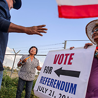072115       Cable Hoover<br /> <br /> AJudy Dahozy, center, and Marge Tom campaign for the Navajo language referendum outside the polling location at the Fort Defiance Chapter House Tuesday.