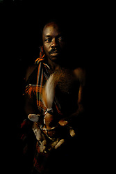 """Ahmad Msham, 39, a bush doctor from Chidodo settlement in Lindi, Tanzania holds a gourd with lion's hair that he uses for """"white magic"""" when spirit lions are thought to be eating villagers. (Photo by Ami Vitale)"""