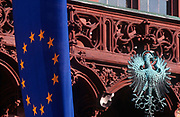 An EU flag and the Prussian Eagle sit side-by-side, on 16th May 2000, in Frankfurt, Germany. The EU flag hangs limply alongside the old German world Prussian eagle near the balcony of Frankfurts Rathaus or Town hall in historic Romerberg Square. The yellow stars formed into a circle of the European Union member states lie on a background of blue but the bronze green eagle harks back to a previous era of German politics and culture. The state of Prussia developed from the State of the Teutonic Order. The original flag of the Teutonic Knights had been a black cross on a white flag. Emperor Frederick II in 1229 granted them the right to use the black Eagle of the Holy Roman Empire.[citation needed] This Prussian Eagle remained the coats of arms of the successive Prussian states until 1947.