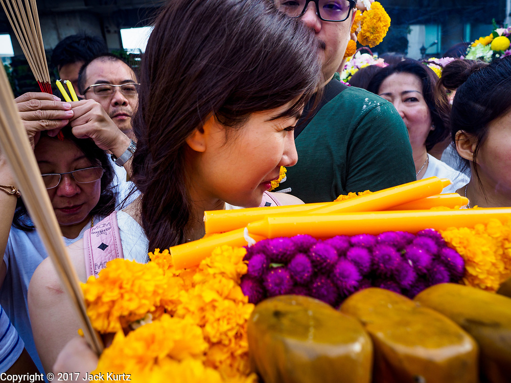 09 NOVEMBER 2017 - BANGKOK, THAILAND:  A woman tries to squeeze through the crowd to find a place to pray at the Erawan Shrine on the 61st anniversary of the shrine's dedication. The Erawan Shrine is one of the most popular shrines in Bangkok. It was dedicated on November 9, 1956, after a series of construction accidents at what was then the Erawan Hotel (since torn down and replaced by the Grand Hyatt Erawan Hotel). The statue in the shrine is Phra Phrom, the Thai representation of the Hindu god of creation Brahma. It is a Hindu shrine popular with Thai and Chinese Buddhists because it is thought that making an offering to the Phra Phrom will bring good fortune.   PHOTO BY JACK KURTZ