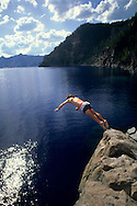 Diver diving into lake water from rock cliff ledge, Cleetwood Cove, Crater Lake National Park, Oregon