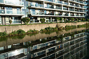Apartment buildings reflected in the water on Lea Navigational Canal in East London, England, United Kingdom.