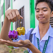 CAPTION: Kin Olahay talks about an initiative to segregate and re-use waste. Plastic bottles are recycled and made into christmas decorations, like these ones. Kin and his fellow students at Parang High School recently attended a climate change workshop run by the local government and facilitated by ACCCRN's implementing partners, ICLEI. This helps to reinforce their knowledge of climate change impacts, mitigation and adaptation, and since attending the workshop they have been more active around their school, practicing mitigation and adaptation solutions and training other students in the same skills. LOCATION: Parang High School, Marikina City, Philippines. INDIVIDUAL(S) PHOTOGRAPHED: Kin Olahay.