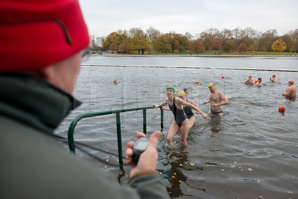 © Licensed to London News Pictures.30/11/2013. London, UK. Competitors climb out of the Serpentine lake after the Serpentine Swimming Club's winter swimming competition in the cold water of the Serpentine Lake in Hyde Park.Photo credit : Peter Kollanyi/LNP