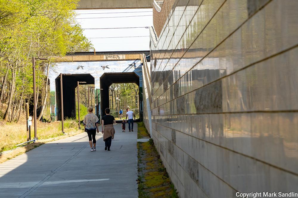 Bike riders, walkers, families and individuals enjoy spring blooms along the Atlanta Beltline. Westside Beltline runs behind homes, industrial parks and sprouting business.