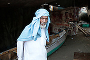An older fisherman stands in his small space, in the background a political poster has been converted into a space divider.  The small fishing village of Machimaar Nagar struggles to hold on as the explosive growth of Mumbai begins to encroach on its space.