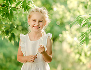 Child wearing light white dress playing in the park with flowers