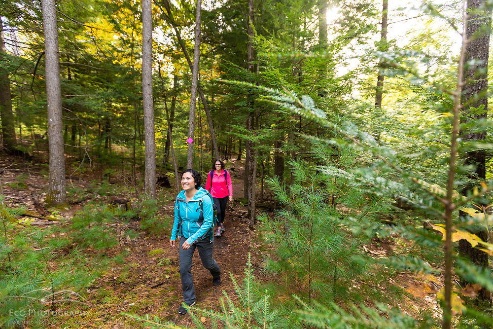 Two women on a hike in the Raymond Community Forest in Raymond, Maine. Fall.