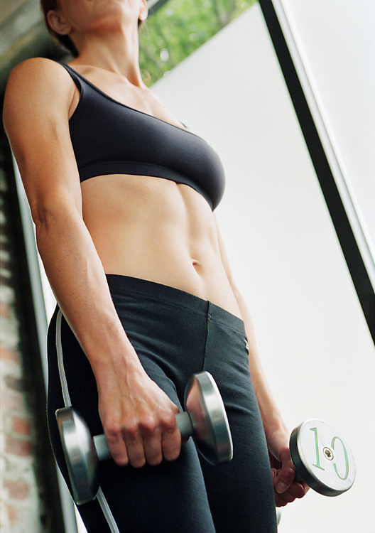 A physically fit woman holding dumbells in a gym setting seen from the chin down to mid leg.