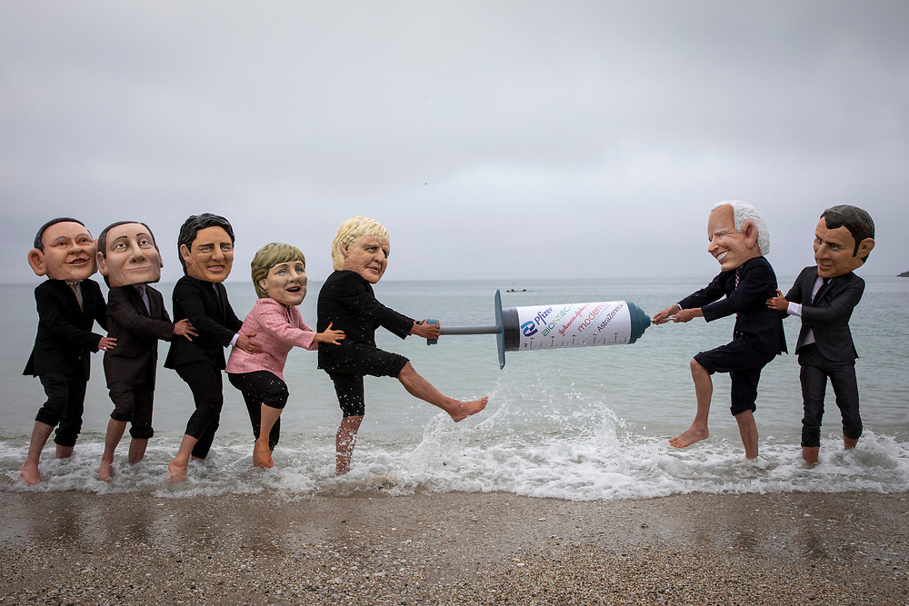 Joe Biden and Emmanuel Macron face off against Boris Johnson and the other G7 leaders in a tussle over a giant syringe, with campaigners for The People's Vaccine Alliance pose as G7 leaders, fighting over a COVID-19 vaccine on the 11th of June 2021 near Falmouth, Cornwall, United Kingdom.US President Joe Biden is the only G7 leader to back a waiver on intellectual property for vaccines that would allow mass production to vaccinate the world. A key issue for the G7 leaders to make an agreement on this weekend at the 47th G7 summit.(photo by Andrew Aitchison/In Pictures via Getty Images)