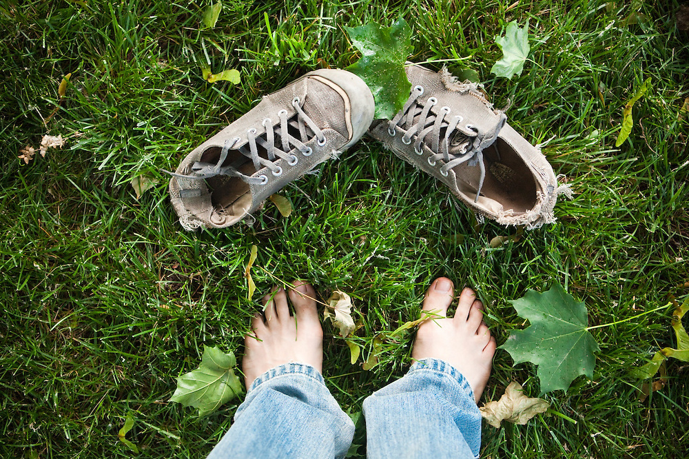 Ethan Welty looks down at a pair of shoes in the grass among fallen leaves in his front yard in Boulder, Colorado.