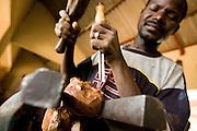 A man makes wooden carvings at the Village Artisanal de Ouagadougou, a cooperative that employs dozens of artisans who work in different mediums, in Ouagadougou, Burkina Faso, on Monday November 3, 2008.