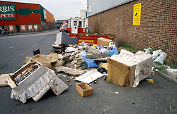 Fly tipped rubbish in front of a sign 'dumping of rubbish prohibited - CCTV in operation'