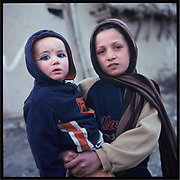 A girl carries her younger sibling in Kabul.