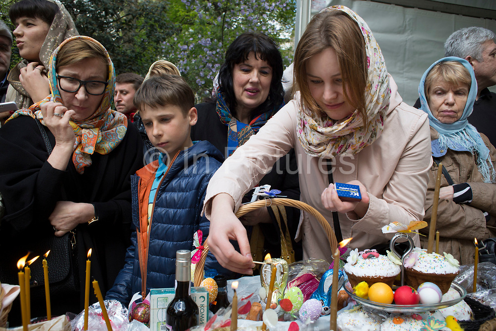 London, UK. Saturday 19th April 2014. Easter celebration gathering of women lighting candles at the Russian Orthodox Cathedral Church on Ennismore Gardens in West London. On this day before Easter Sunday Russians gather in a religious festival where their painted eggs; traditional cakes and other offerings are blessed. Then at midnight will be offered to God. Nothing is expected in retun in terms of good fortune.