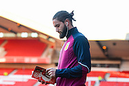 Aston Villa midfielder Henri Lansbury (5) reads the Forest Review match day program on the pitch ahead of the EFL Sky Bet Championship match between Nottingham Forest and Aston Villa at the City Ground, Nottingham, England on 4 February 2017. Photo by Jon Hobley.