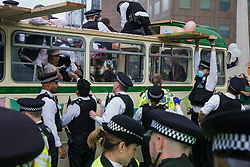 Metropolitan Police officers take control of a vintage bus used by environmental activists from Extinction Rebellion to block a road junction to the south of London Bridge on the ninth day of their Impossible Rebellion protests on 31st August 2021 in London, United Kingdom. Extinction Rebellion are calling on the UK government to cease all new fossil fuel investment with immediate effect.