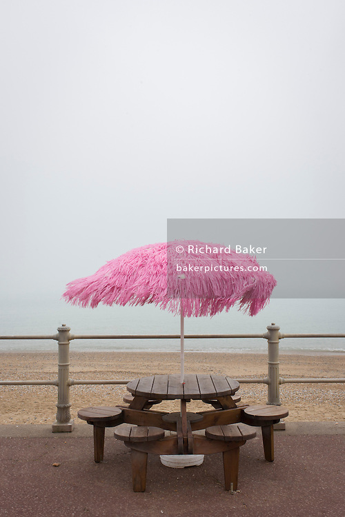 A pink-coloured parasol blows in the wind on a seafront during the winter off-season