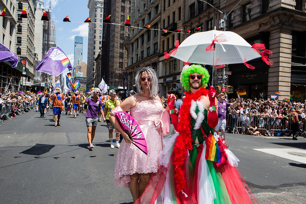 """New York, NY - 30 June 2019. The New York City Heritage of Pride March filled Fifth Avenue for hours with participants from the LGBTQ community and it's supporters. Two men in dresses, one of who carries a fan that reads """"Bitchy."""""""