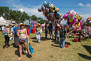 Balloon sellers in the main arena. WOMAD 2014, festival of world music and dance, Charlton Park, Wiltshire. UK.