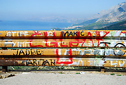 Section of graffiti covered safety fence, with foothills, the slopes of Biokovo National Park and the Adriatic Sea in the background. Near Makarska, Croatia