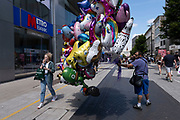 People pass helium filled balloon seller in the city centre on 14th July 2021 in Birmingham, United Kingdom. These balloons, all being held in a large bunch depict all sorts of characters from cartoons and tv.