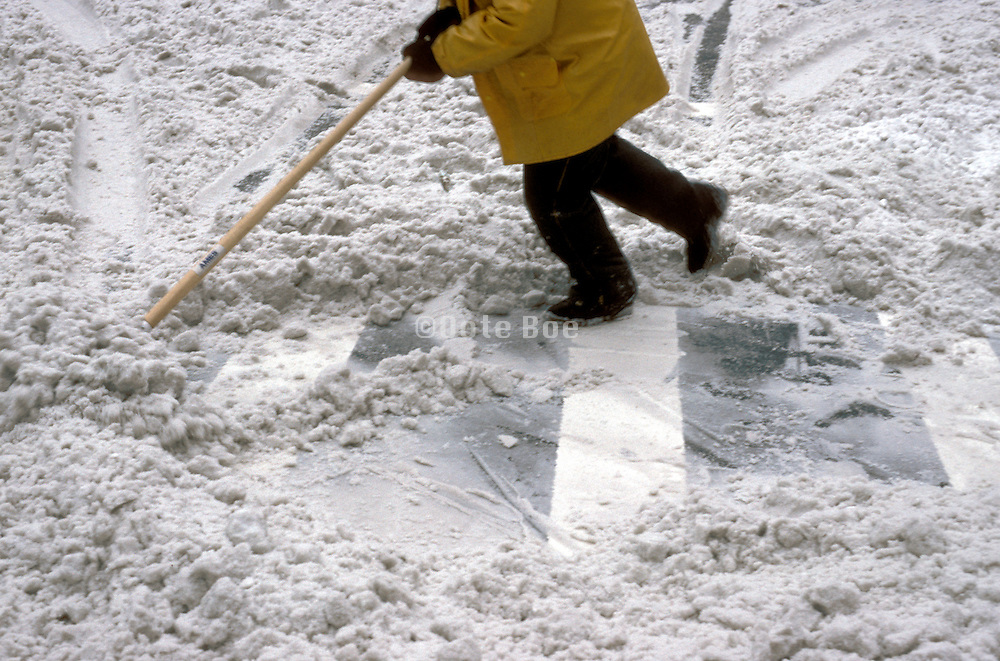 man clearing snow of pedestrian pad