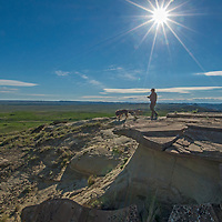 A hker and his dog stand explore eroded rock features in Charles M. Russell National Wildlife Reserve, Montana.